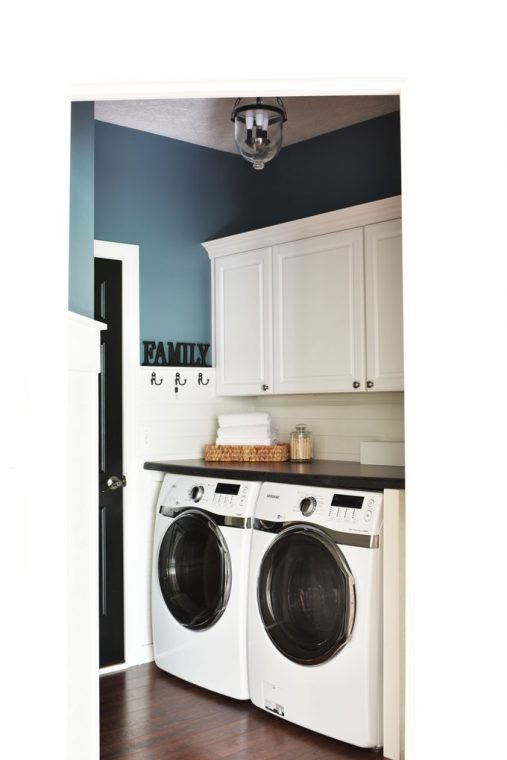 Blue and white shiplap laundry room with a counter over the washer and dryer.