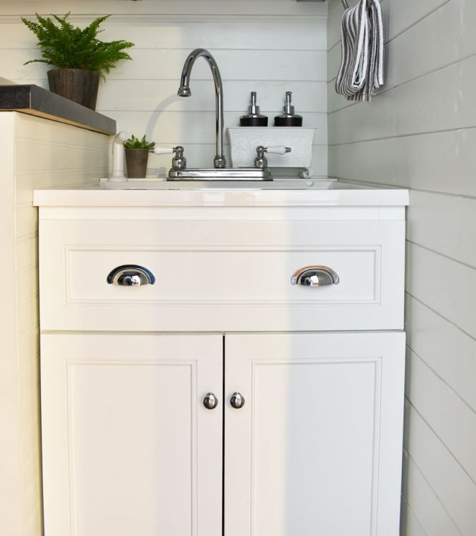 White farmhouse laundry room sink with a white shiplap background.