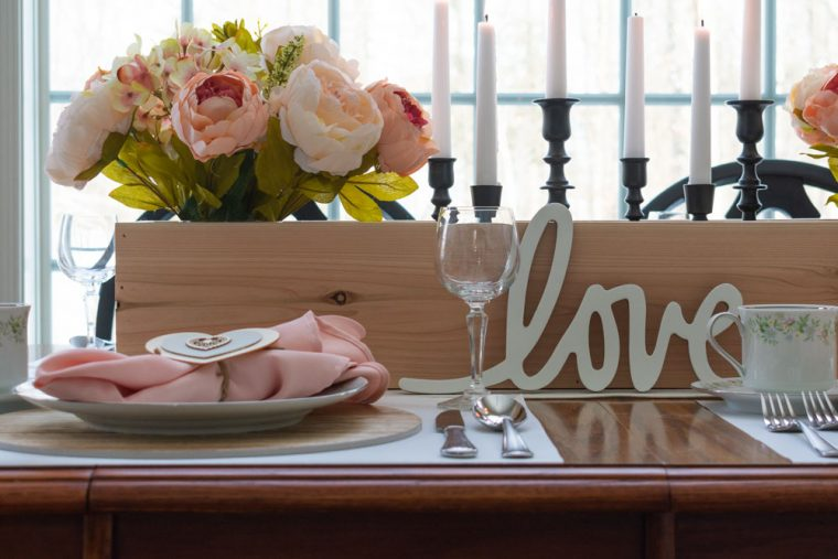 Budget Friendly Valentine's Day Tablescape with wood cedar planter, blush & white flowers and black candlesticks.