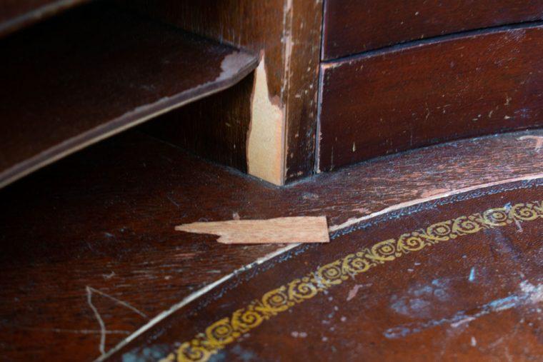 Updating peeling wood veneer on an antique piece of furniture.