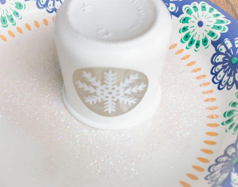 Adding glitter to the edge of a DIY votive holder.