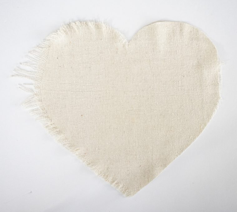 Fraying the edge of fabric drop cloth to make a fringe heart.