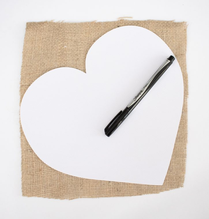 Tracing a card-board heart template to make a burlap heart.