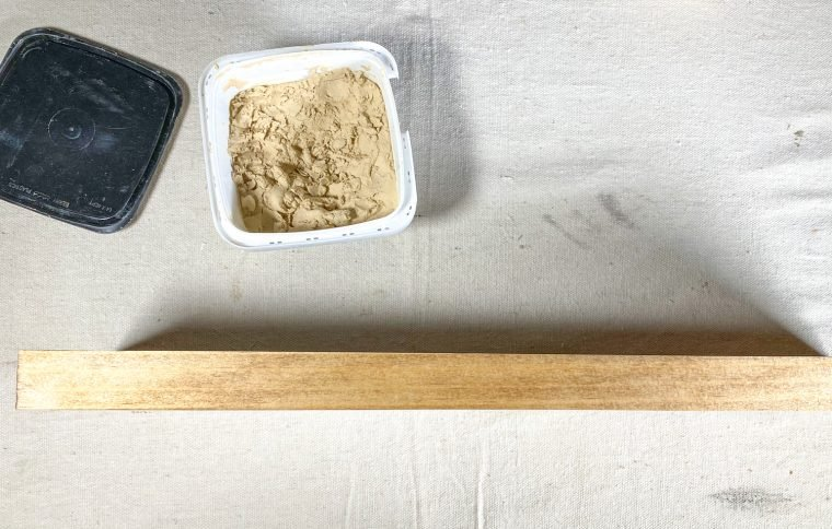 Use wood filler in the nail holes of your herb planter base.