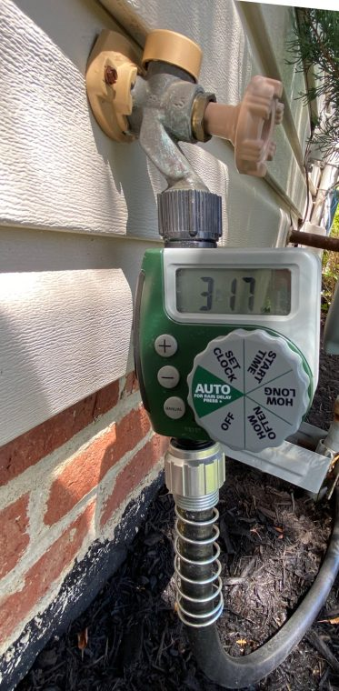 Timer attached to outside faucet for a hose to water trees.