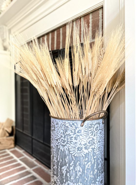 Decorative wheat display on a fireplace hearth.