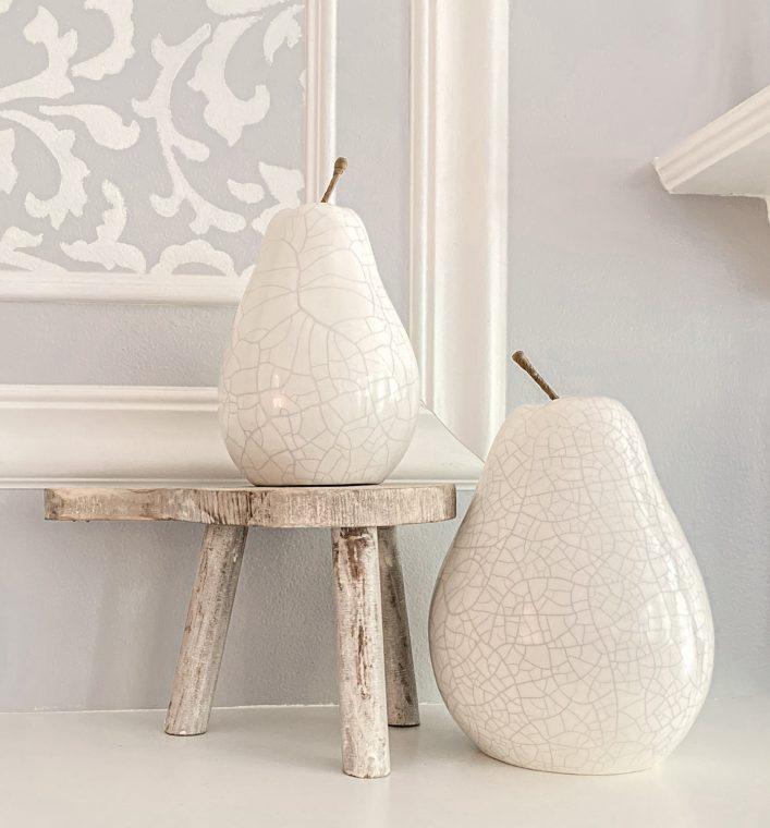 White ceramic pears decorating an accent shelf for fall.