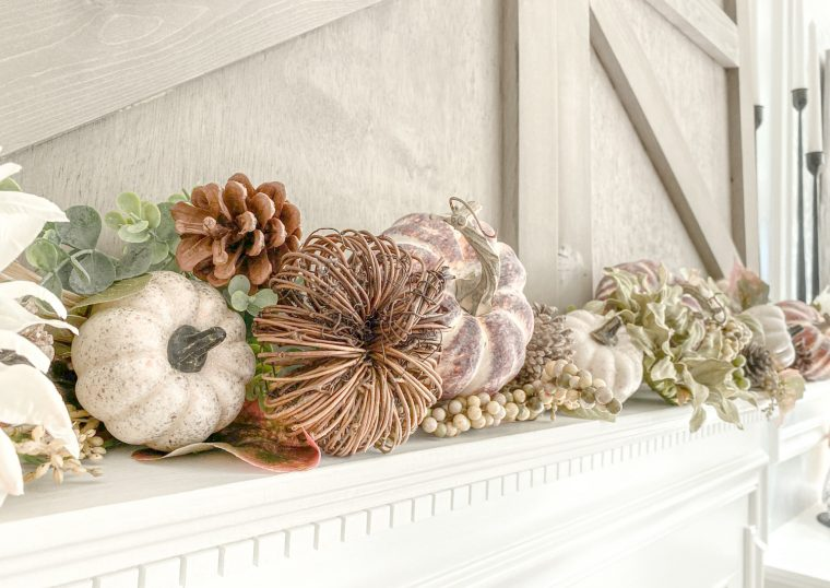 Pumpkins and natural elements decorate a fireplace mantel for autumn.