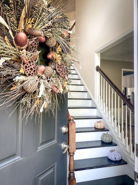 Fall entryway with natural wreath and pumpkin luminaries.