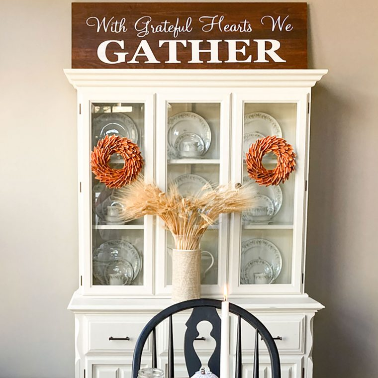 Fall decorations on a dining room hutch.
