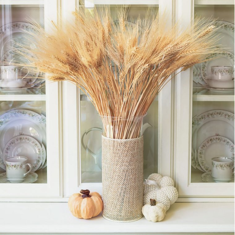 Wheat as fall decor on a dining room hutch.
