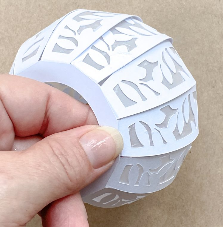 Add the extra panel to the bottom of your paper pumpkin to finish your craft.