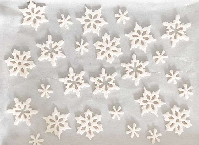 Snowflake ornaments on parchment paper to be dried in oven.