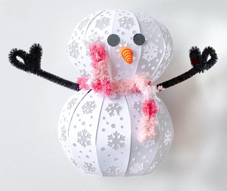 Assembling a 3D paper snowman craft.