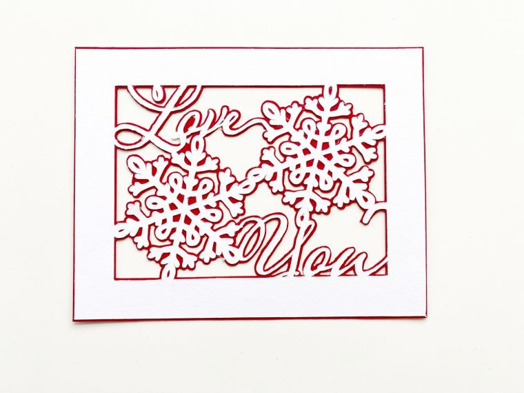 Assembling a handmade Valentine's card created with a free SVG and cutting machine.
