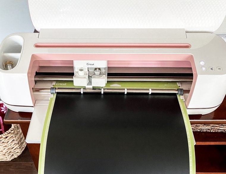 Loading a Cricut cutting mat into a Cricut machine for cutting vinyl.
