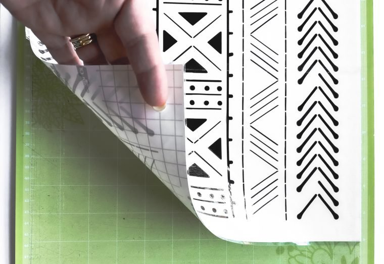 Lifting the vinyl with transfer tape off of a Cricut cutting mat.