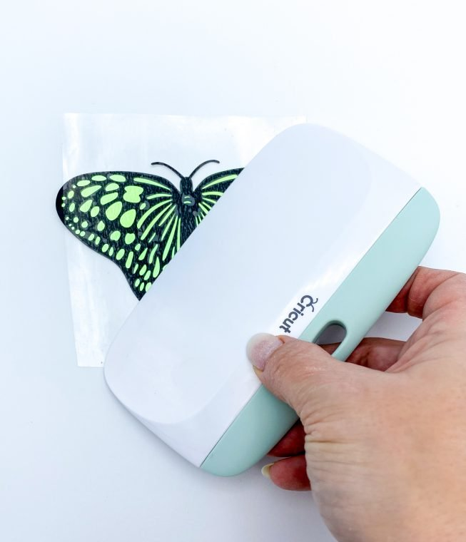 Using transfer tape to attach a vinyl cut butterfly pattern to holographic paper for a 3D effect.
